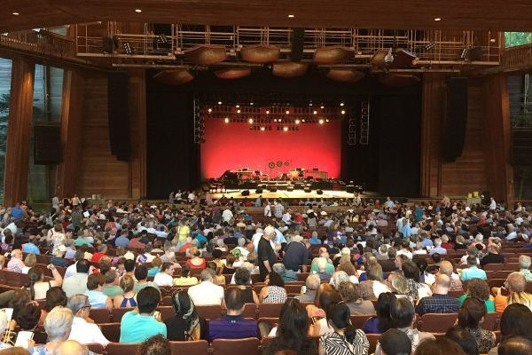 Fairfax, VA Wolf Trap Park for the Performing Arts, large wooden outdoor theater, semi-covered seating, stage set with black grand piano and other instruments.