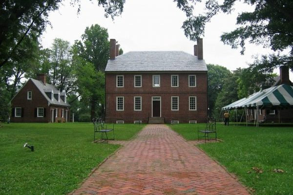 Kenmore Plantation in Fredericksburg VA, two story brick home with slate roof, lush green lawn with tent ready for outdoor event.