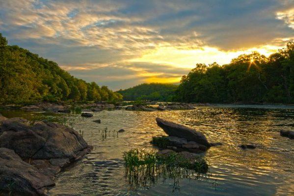 Fredericksburg, VA Rappahannock River sunrise over water, rocks, and tree-filled banks.