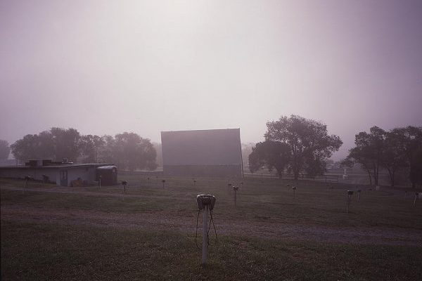 Lexington, VA Hull's Drive In, famous local drive in field of parking spaces with speaker boxes and large screen during foggy morning.