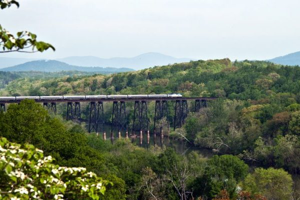 Lynchburg, VA James River Trestle train crossing high iron bridge over James River, green trees on either side of valley.