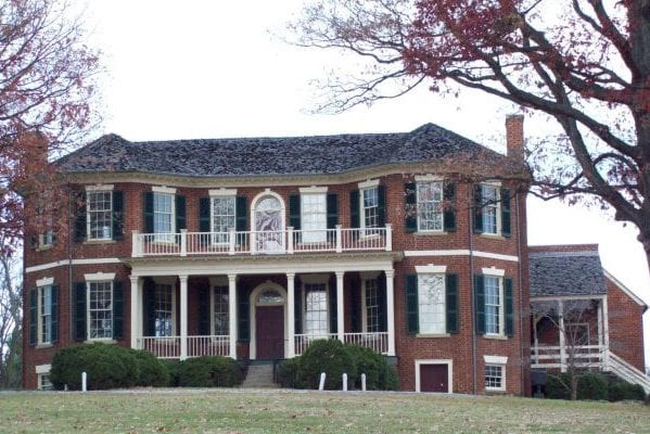 Lynchburg, VA Point of Honor museum, two story red brick home with double decker front porch, cedar roof, red fall leaves on trees.