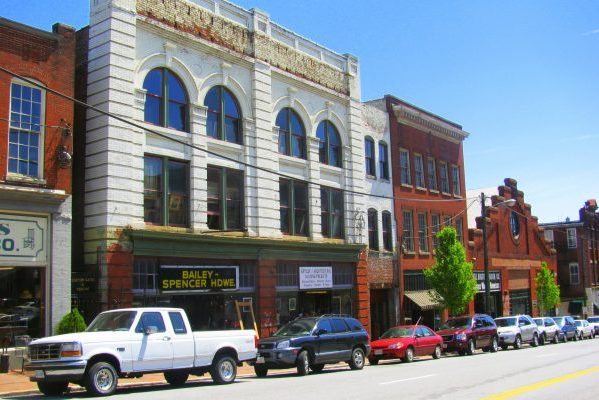 Lynchburg, VA downtown red brick storefronts lining Main Street, line of cars parked against curb.