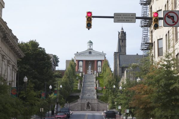 Lynchburg, VA red brick, red columned museum atop tall hill with wide concrete stairs climbing the hill to entrance.