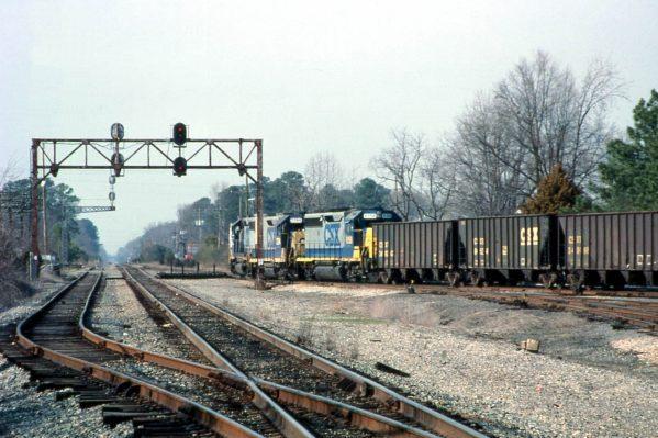 Newport News, VA CSX Railroad two blue CSX railroad engines pulling line of empty coal cars on railway.