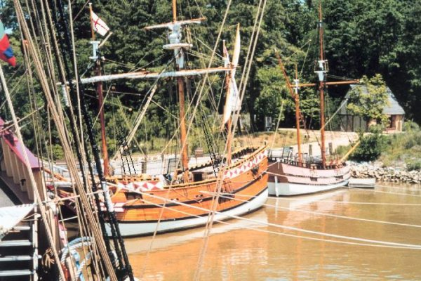 Newport News, VA Jamestown settlement area, three large reproduction multi-masted wooden sailing ships lashed to a dock.