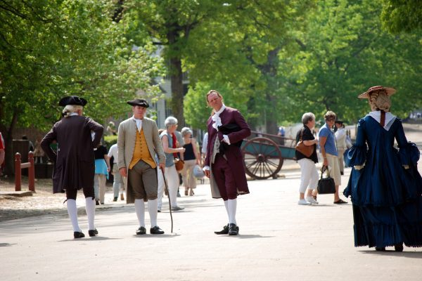 Newport News, VA Williamsburg street filled with people and carts in period garb, long woolen coats, black triangular hats, long dresses.