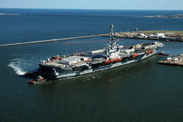 Newport News, VA shipyard aerial view of large aircraft carrier being piloted into berth by tugboats.