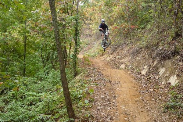 Danville, VA Anglers Ridge Mountain Bike Trail, mountain biker jumping hills on dirt trail between trees.