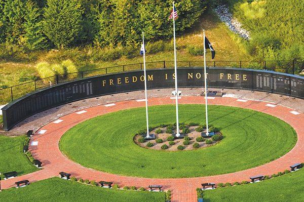 Danville, VA Dan Daniel Memorial Park, aerial view of memorial wall and surrounding green lawn. Three flags in center.