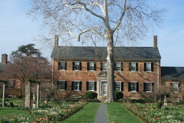 Fredericksburg, VA Chatham Manor, sprawling two story brick home with slate roof and gardens with tulips in front.