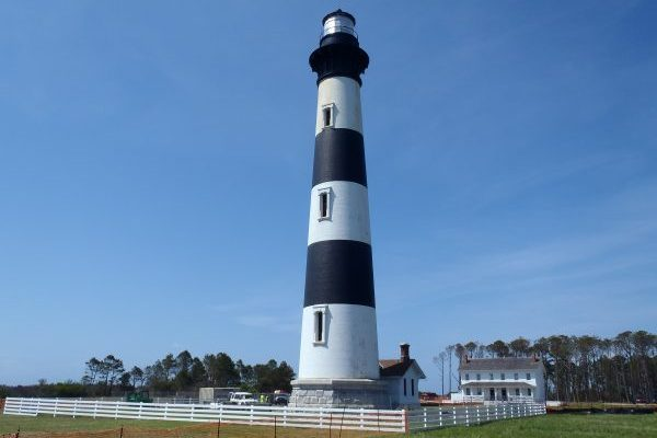 Outer Banks, NC Bodie Island Lighthouse, tall black and white striped lighthouse in green field with blue sky background.