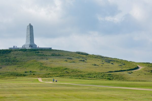 Outer Banks, NC Wright Brothers National Memorial limestone triangular-shaped spire about seventy-five feet high, atop a shrub-covered dune.