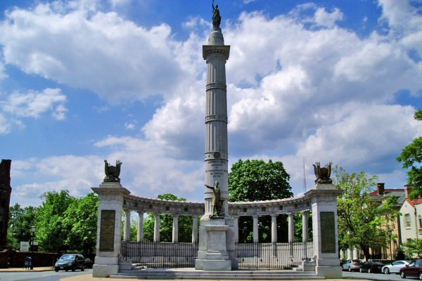 Richmond, VA Monument Avenue view of a tall limestone column with bronze statue at bottom of a man in coat pointing, surrounded by lower limestone wall with yet more columns.