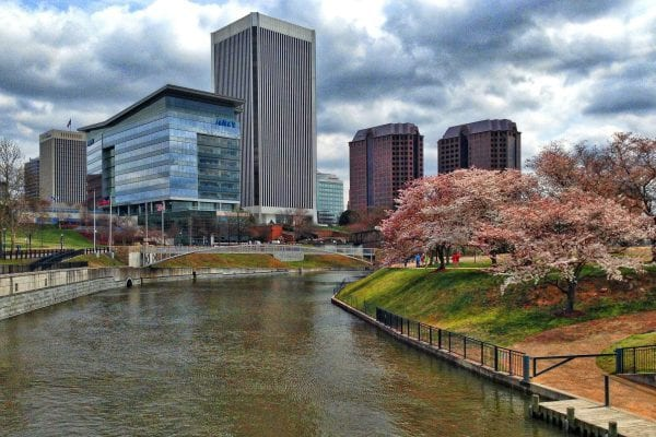 Richmond, VA canal with highrises on one side and Brown's Island on the other with green grass and budding cherry trees.