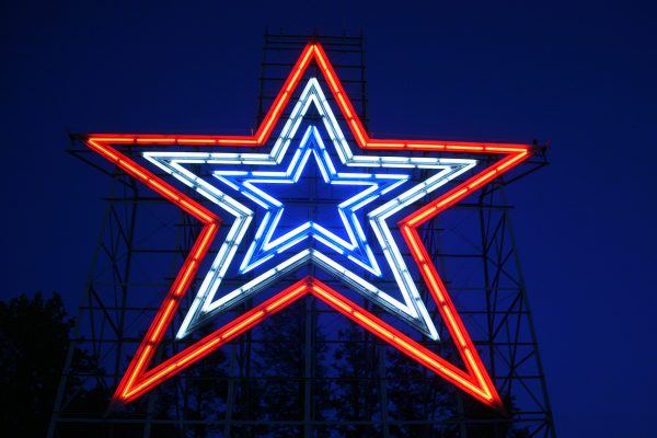 Roanoke, VA Mill Mountain Star shown at night, blue neon center with repeated larger neon lights in white and red surrounding it.