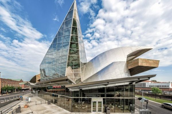 Roanoke, VA Taubman Museum of Art, a large, modern, glass, metal, and stone structure with tall glass triangular-shaped spire extending ten stories from a stainless steel sided wave-shaped structure covering a large stone-slabbed balcony overlooking surrounding city streets.