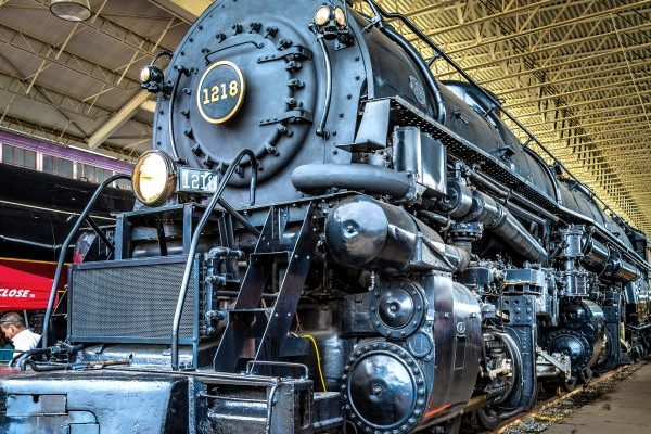 Roanoke, VA huge black steam locomotive beneath metal trussed canopy in the Virginia Museum of Transportation.