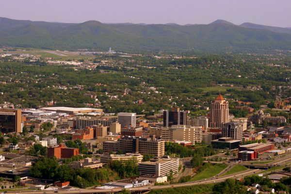 Roanoke, VA view of entire downtown area of the city, tall buildings in foreground, green mountains in background.