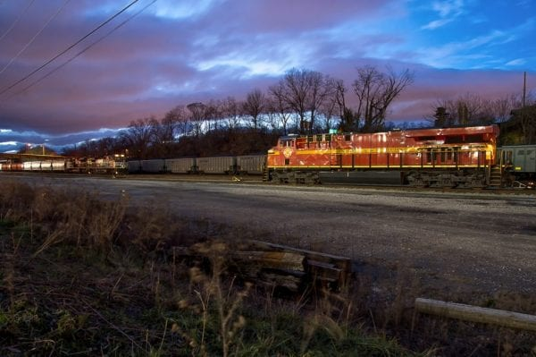 Roanoke, VA red and yellow train engine in South Yard with bulk carrier cars and tank cars on tracks behind it, at dusk with purple and blue clouds above.