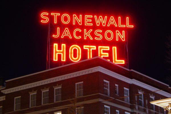 Staunton, VA Stonewall Jackson Hotel, iconic neon orange sign glowing atop tall brick hotel.