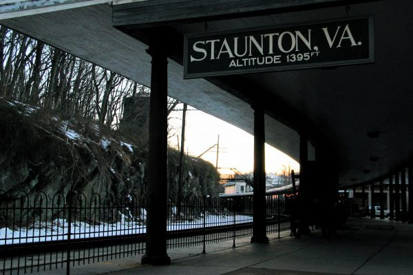 Staunton, VA train station, covered passenger area with sign stating altitude of 1395 feet, next to train tracks, decorative black iron fence separating them.