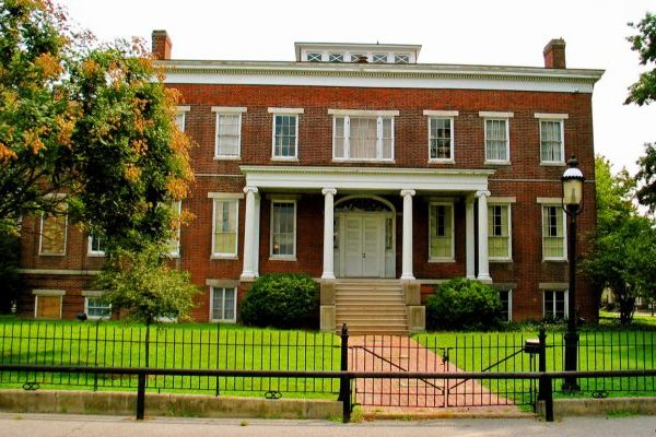 Sutherland, VA Centre Hill Mansion large two-story brick home with single-story four columns forming front portico, black iron fence in foreground.