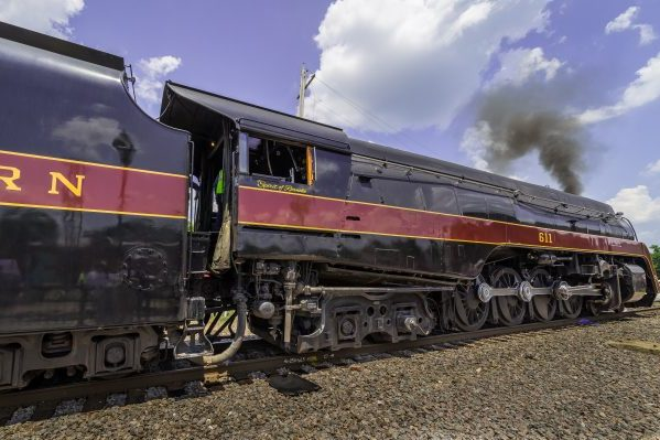Sutherland, VA Norfolk & Western 611, closeup of sleek shiny black train engine with dark red stripe, black smoke rising against blue sky.
