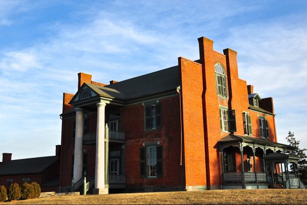 Wytheville, VA The Mansion at Fort Chiswell, a grand, three story brick home with tile roof, green shutters, and two tall columns out front forming two-story porch.