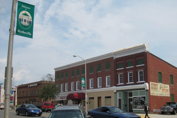 Wytheville, VA downtown street with three story brick mercantile buildings and green and white Wytheville sign in foreground on street lamp pole.