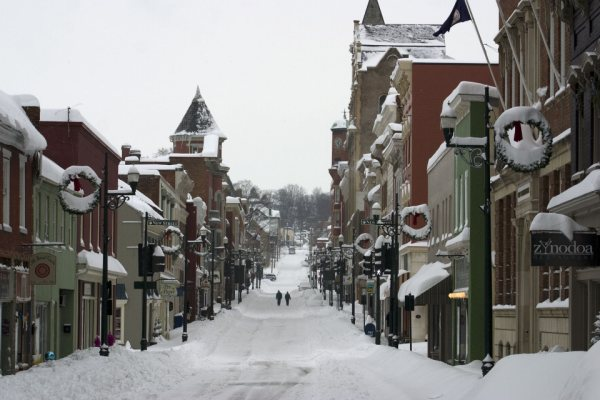 Staunton, VA snowy downtown street filled with snow, flanked by multi-colored shops and buildings, all piled with snow, circular wreaths on light poles.