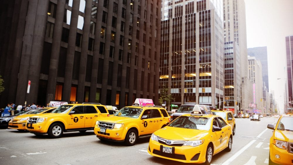 Cancellation Clause Transportation Contracts, a row of yellow taxis of all varieties, SUV and sedan, in a city with high rises in background.