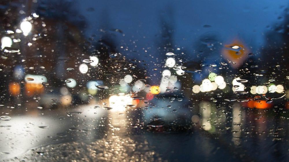Flood Insurance Waiting Period Insurance Moratoriums, blurry twilight view of lighted street through wet window.