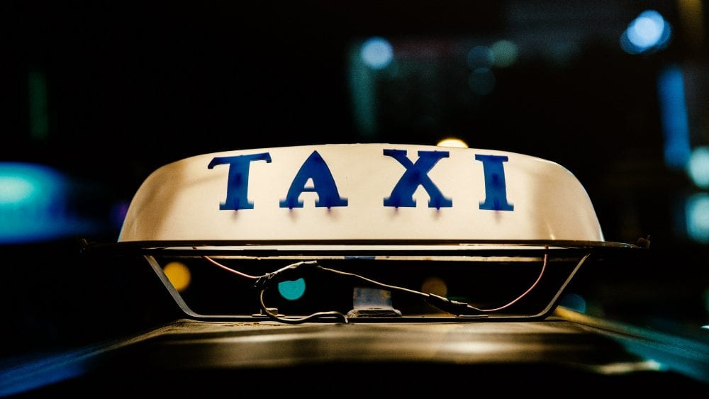 Old taxi sign atop a vehicle, lighted and at night, blue letters on white.