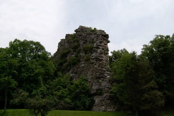 Large brown rock wall flanked by green trees near our Bluefield WV insurance agency, Pinnacle Rock State Park.
