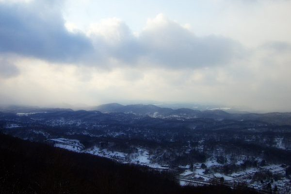 Winter overlook of Bluefield, WV insurance agency, snowy winter valley with low clouds.