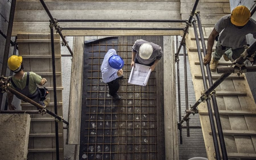 Construction workers and architects at a construction site viewed from above.