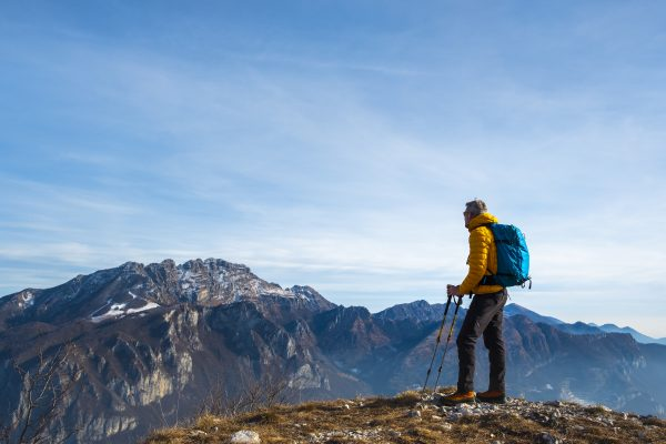 Hiker on mountain overlooking mountainous landscape, symbolic of partnering with us to sell your insurance agency.