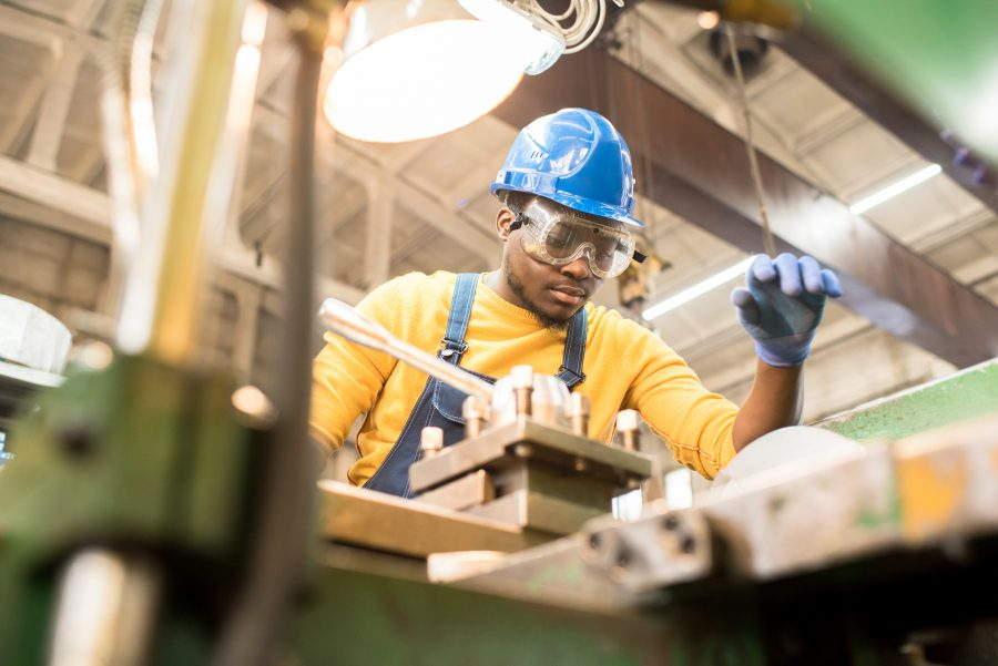 Worker with gloves, hardhat, and eye protection to control workers compensation insurance costs works on metal working machine.