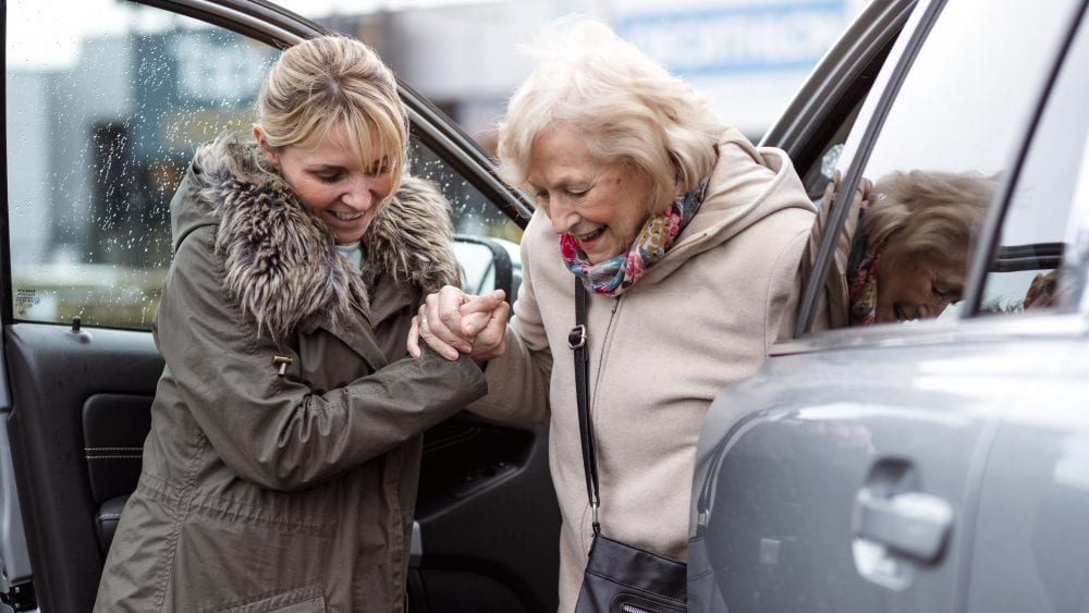 Lady helping older woman out of car, symbolizing question of who is covered under an auto insurance policy.