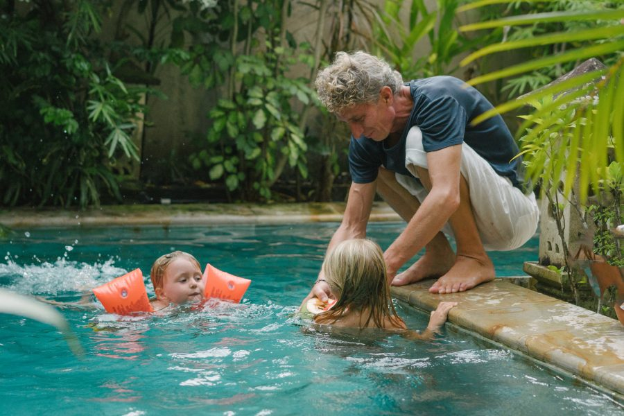 Homeowners insurance red flags, father watching daughters in unfenced swimming pool.