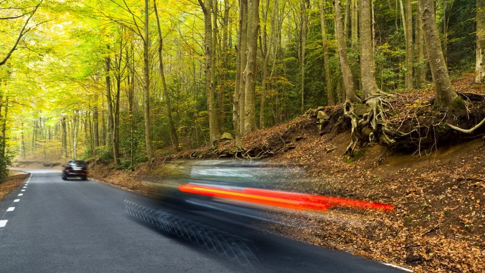 Two cars on a mountain road motion blur. Insurance pays.
