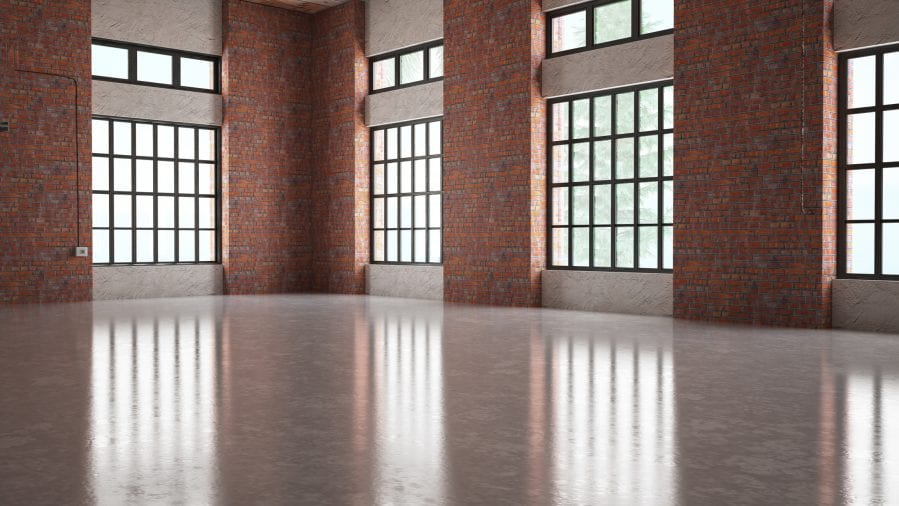 Modern brick warehouse interior, representing how replacement cost valuation method replaces old materials with new of like kind and quality.