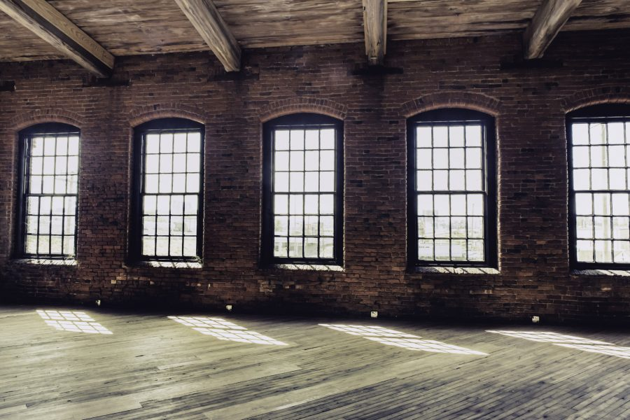 Windows in an old brick warehouse with wooden floor. Actual Cash Value insurance valuation method considers depreciation of the structure.
