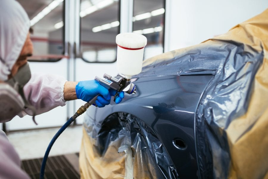 Man with protective clothes and mask painting car using spray compressor. Claim paid by uninsured motorists protection.