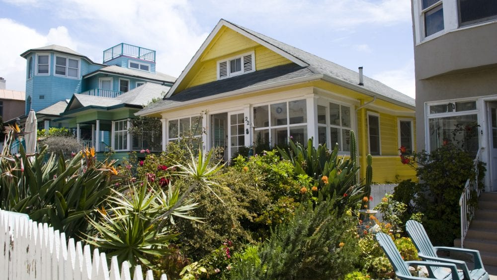 Colorful beach houses with white picket fence for home-sharing and rental insurance.