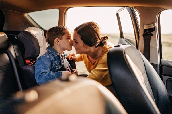 Mother buckling up young son in car seat, protected by collision car insurance.