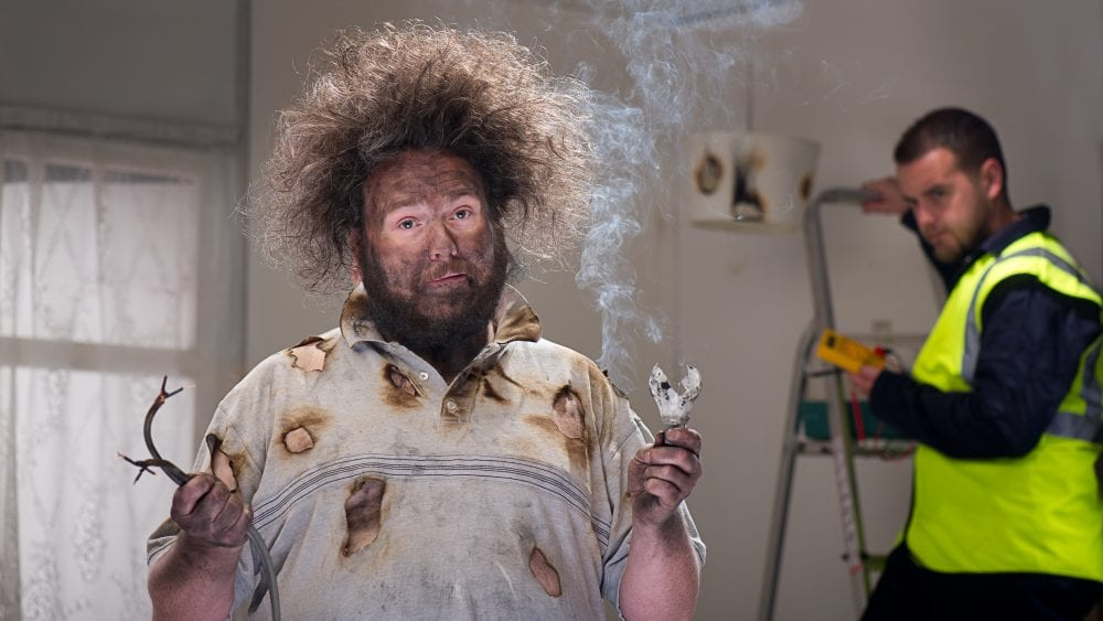 A man with burned face and frizzy hair holding smoking frayed electrical wires demonstrating common electrical wiring issues.