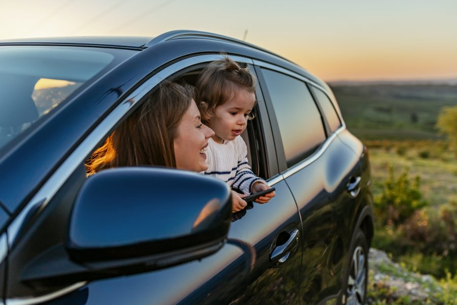 Woman and child in car on side of road enjoying the view, representing car insurance client.