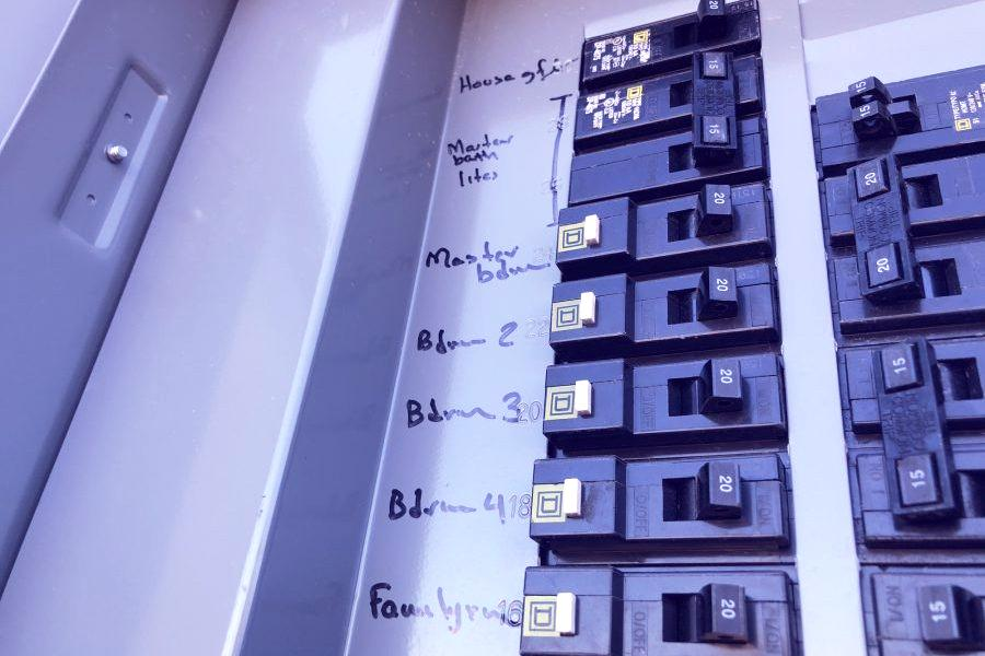 Gray metal box with two rows of black circuit breakers.